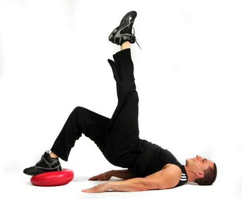 Say goodbye to flabby abs with the single leg bridge. It can be done on the floor if you don't have a disc. Photo: Joey Ivansco, AJC