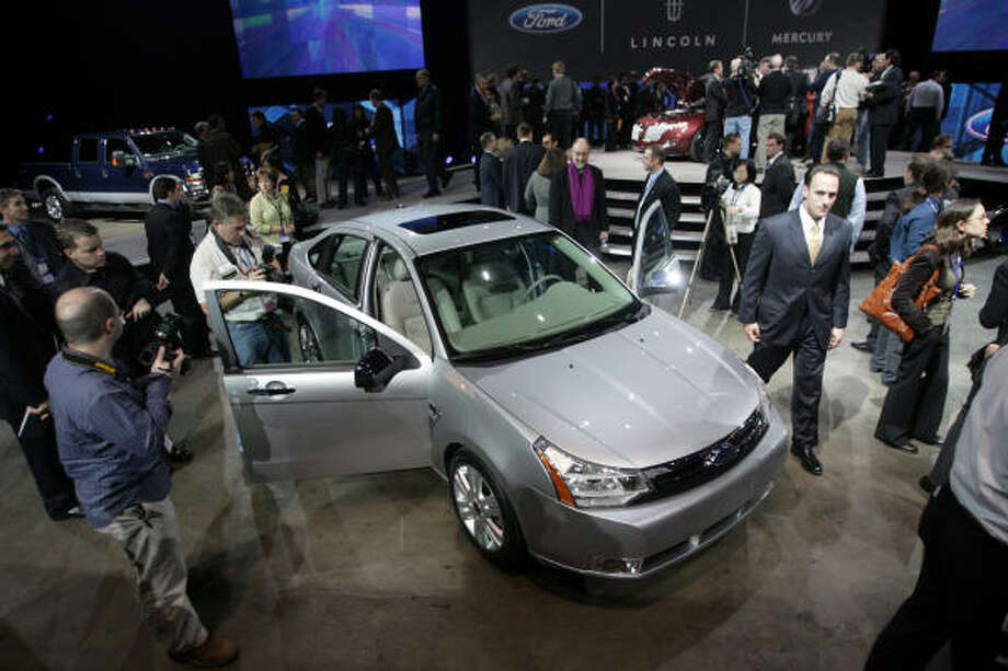 Members of the news media gather around the 2008 Ford Focus, which is equipped with voice-activated software to let the driver make phone calls and play songs from a digital music player. Photo: Rashaun Rucker, DETROIT FREE PRESS