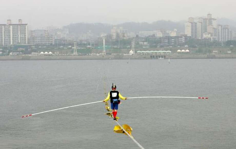 Pedro Carrillo of of Reno, Nev., crosses the Han River on Thursday in the first World High Wire Championships in Seoul, South Korea. Photo: CHUNG SUNG-JUN, GETTY IMAGES