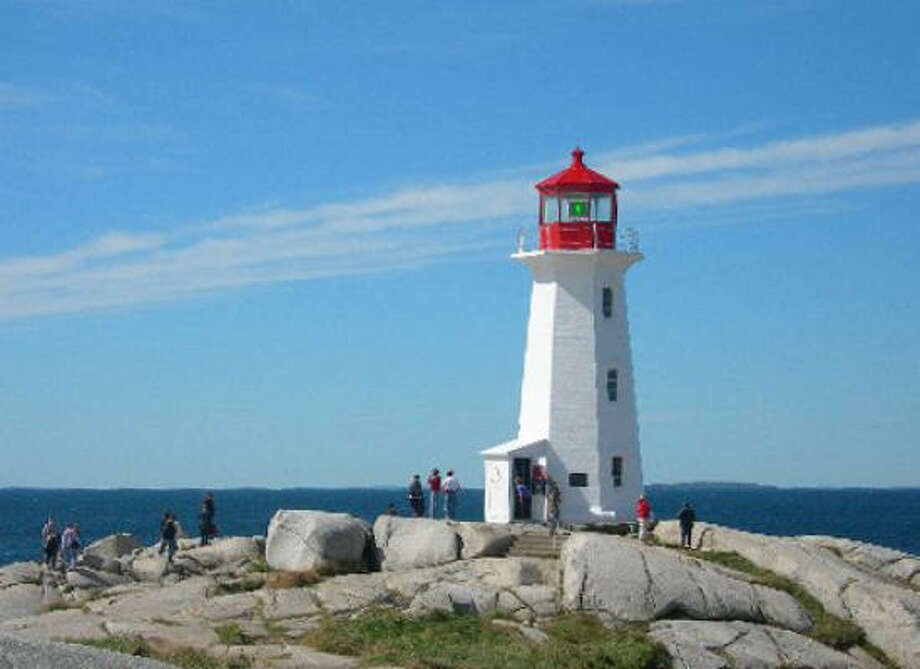 Visitors from the Norwegian Dawn traverse the rocky shore for a look at the landmark lighthouse. Photo: Eileen McClelland, Chronicle