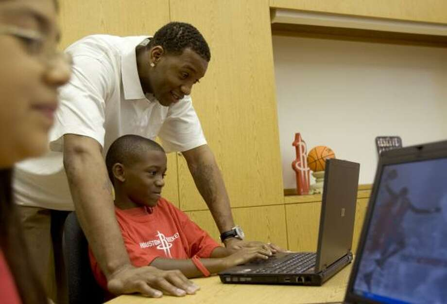 Rockets forward Tracy McGrady looks over the shoulder of fourth-grader Deron McGuire, 10, during the opening of a learning and technology lab at Betsy Ross Elementary in the Fifth Ward on Thursday. Photo: BRETT COOMER, CHRONICLE