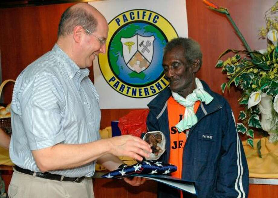 """This image provided by the U.S. Navy shows Secretary of the Navy Donald C. Winter presenting Eroni """"Aaron"""" Kumana with the flag from USS Peleliu for his courageous efforts more than 60 years ago. During World War II, Kumana rescued Lt. John F. Kennedy, and his PT-109's crew following the ship's Aug. 2, 1943, collision with a Japanese destroyer near Pudding Island. Photo: Mass Communication Specialist Se, AP"""