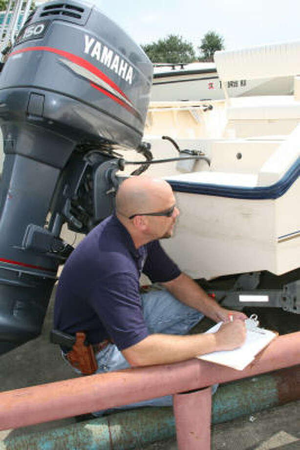 Sgt. Ned Nichols, one of three officers in the TPWD's Marine Theft Unit, conducts an inventory of boats and motors at a Houston-area business. Photo: Shannon Tompkins