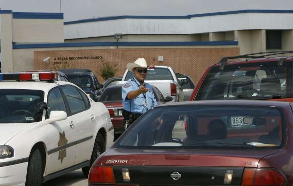 Cypress-Fairbanks ISD Officer R. Hernandez stops cars at Dean Middle School after a student allegedly pointed a gun.