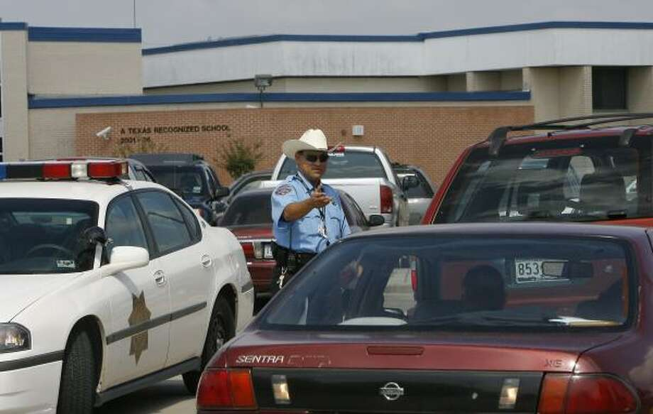 Cypress-Fairbanks ISD Officer R. Hernandez stops cars at Dean Middle School after a student allegedly pointed a gun. Photo: STEVE CAMPBELL, CHRONICLE
