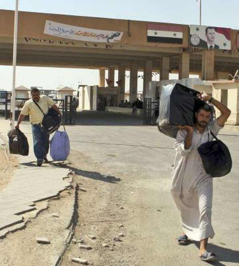 Iraqi refugees head home through the Tanaf border crossing between Syria and Iraq. A Syrian immigration official estimated that up to 1,500 Iraqis were returning to Iraq each day. Photo: BASSEM TELLAWI, ASSOCIATED PRESS