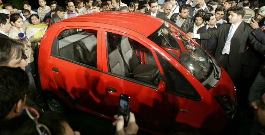 "Members of the news media surround the new Tata ""People's Car"" on Thursday in New Delhi. Photo: MUSTAFA QURAISHI, ASSOCIATED PRESS"