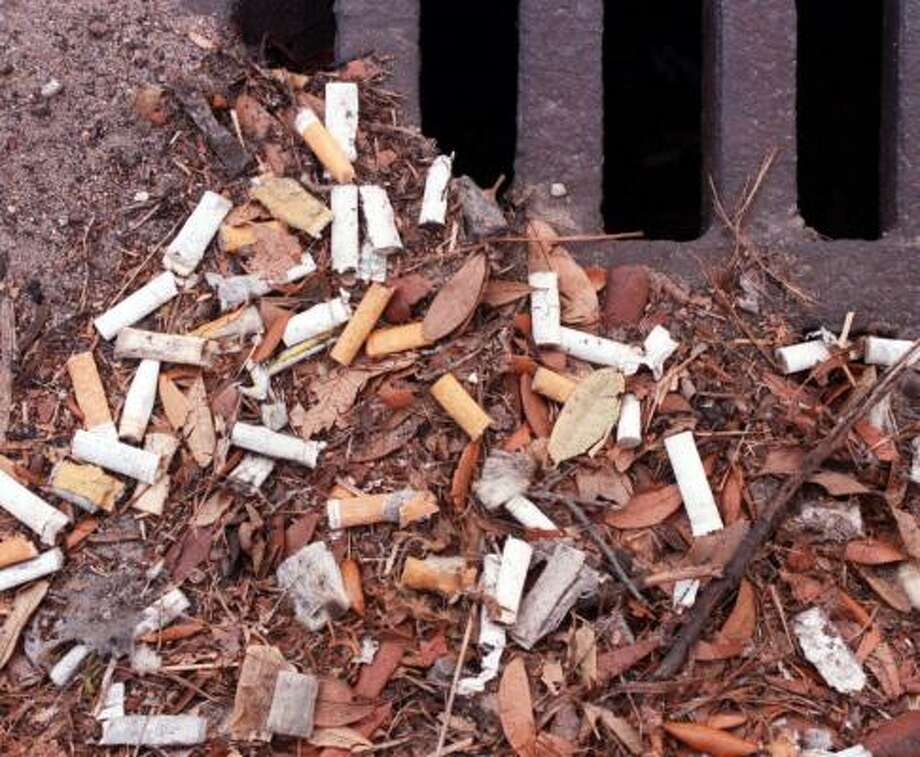 Cigarette butts, like these at a street drainage grate in Gulfport, Miss., in February 2000, are the most common form of litter in the United States and the rest of the world. Litter has decreased about 2 percent a year over the last 30 years in communities where it's been measured. Photo: JOHN FITZHUGH, BILOXI SUN HERALD FILE