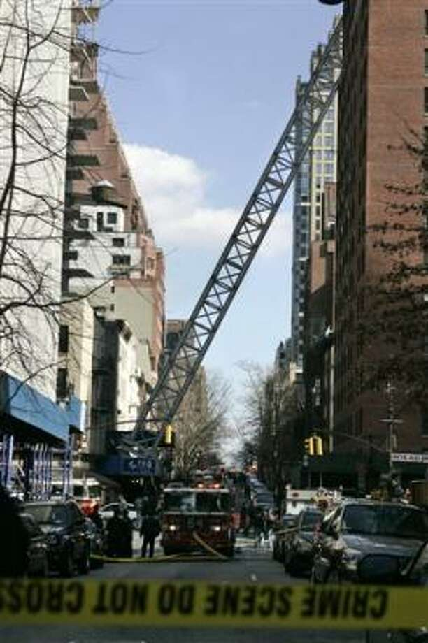 A crane leans between two buildings on 51st Street in New York on Saturday. Photo: Frank Franklin II, Associated Press
