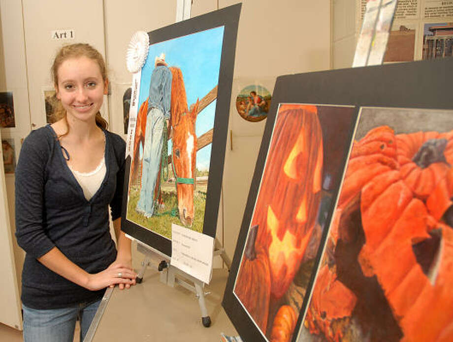 The Woodlands High School senior Courtney Mayo stands by some of her award winning paintings in her art class. She has had a good year winning several art contests. Photo: David Hopper, For The Chronicle