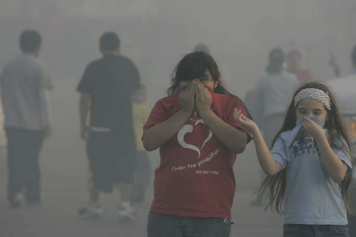 Josselin Aguiluz, 11, center and Kimberly Manqueros, 9, deal with the smoke as they watch the fire. Neither of the girls lived in the apartments.