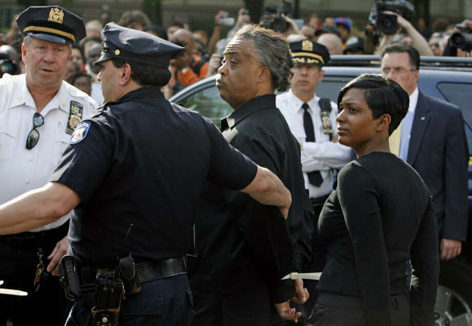 The Rev. Al Sharpton, center, and Sean Bell's fiancee, Nicole Paultre Bell, are led away in handcuffs after being arrested at the Brooklyn Bridge on Wednesday. Photo: Jason DeCrow, Associated Press