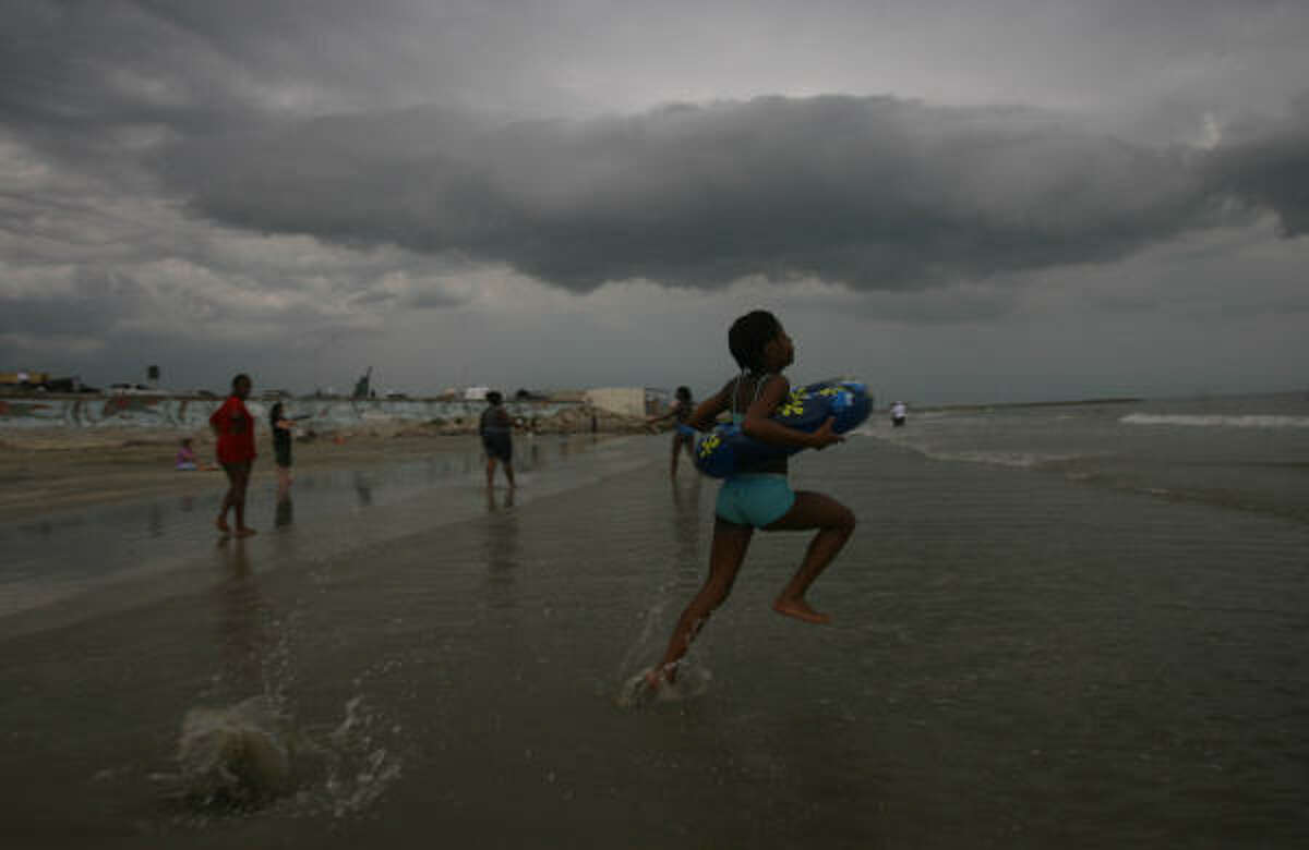 Anjunique Anderson, 11, runs to dive into the water as the waves pick up on Galveston beach on Sunday.