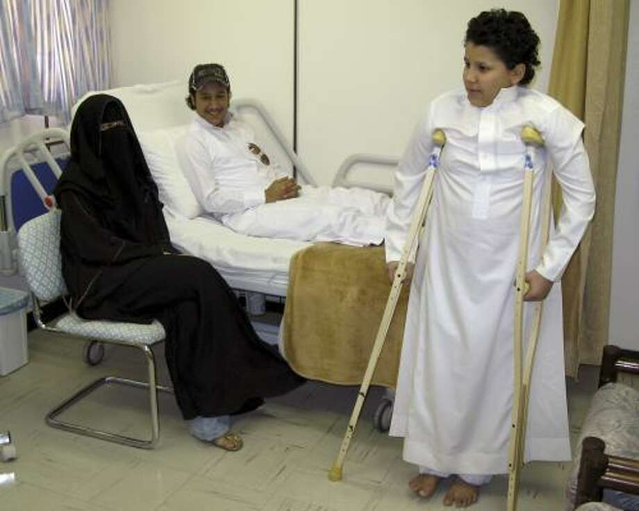 Ruwaida al-Habis, left, sits next to her two injured brothers, Muhammad, center, and Al-Hassan, who uses his crutches, at a hospital in Riyadh, Saudi Arabia. Photo: HASSAN AMMAR, ASSOCIATED PRESS