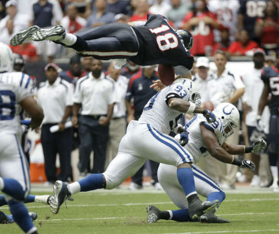 Airborne Texans quarterback Sage Rosenfels is hit by Colts defensive end Dwight Freeney (93) and defensive tackle Raheem Brock (79), forcing a fumble that was picked up and returned for a touchdown by Colts linebacker Gary Brackett. Photo: Brett Coomer, Chronicle