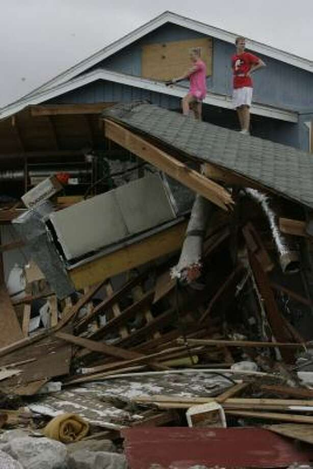 Kara Bridwell, left, and her brother Paul Bisso stand on the roof of a neighbor's house that struck their home in Surfside Beach. Photo: JULIO CORTEZ, CHRONICLE