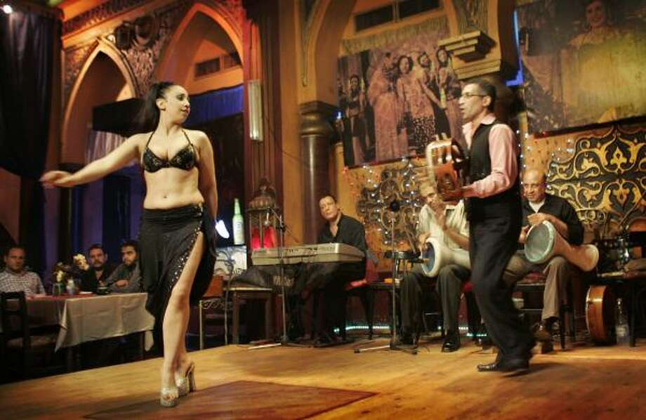 A belly dancer performs at the Shahrazad nightclub in Cairo, Egypt. The club, with 30-foot-high ceilings and velvet curtains, was renovated by Egypt's largest alcoholic beverage company — part of an effort to restore downtown establishments. Photo: BEN CURTIS, ASSOCIATED PRESS