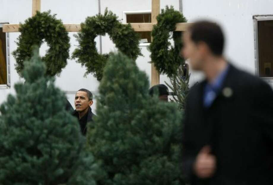 President-elect Barack Obama shops for a Christmas tree in Chicago on Sunday. A Secret Service agent, right, keeps watch. Photo: GERALD HERBERT, ASSOCIATED PRESS