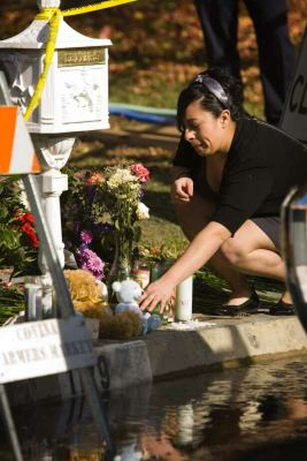 An unidentified mourner visits a memorial in front of the victims' burned home in Covina, Calif., on Saturday. Photo: Liz O. Baylen, Los Angeles Times