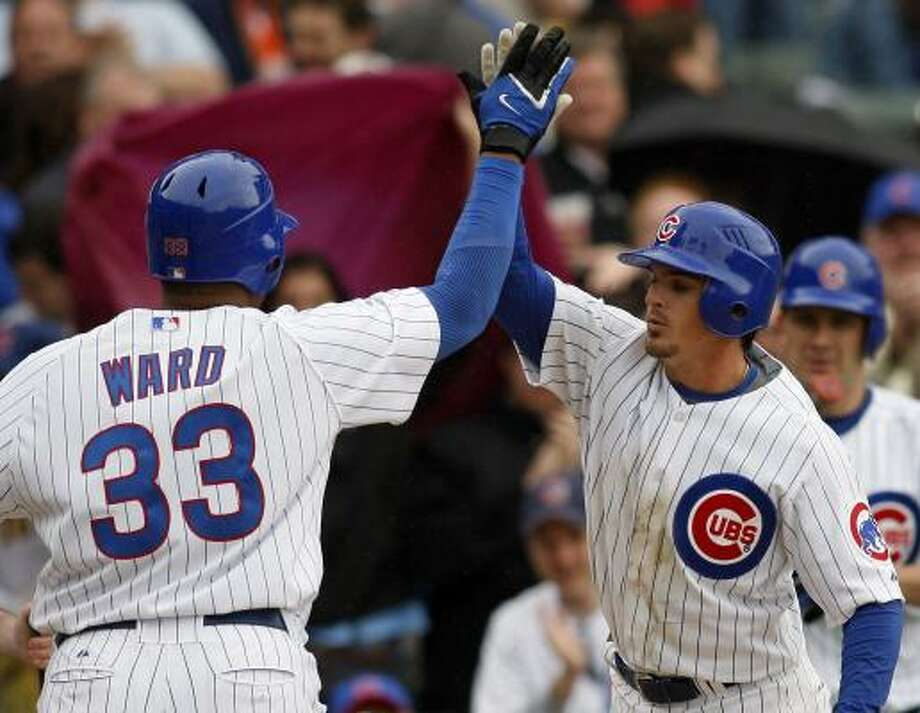 Daryle Ward (33) is congratulated by Chicago teammate Ryan Theriot after hitting a two-run homer in the eighth inning of the Cubs' 13-1 rout of the Pittsburgh Pirates at Wrigley Field. Photo: JERRY LAI, ASSOCIATED PRESS
