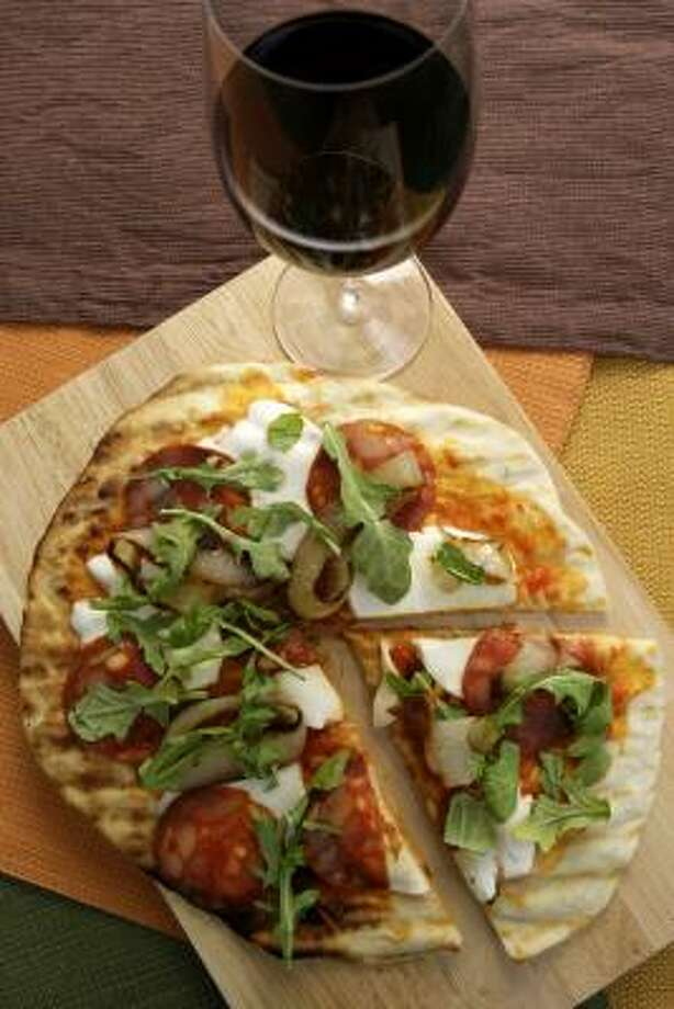 For people who love to cook out but want a light dinner, Smoked Chorizo Pizza With Caramelized Onions and Arugula is the perfect solution. Photo: KAREN WARREN PHOTOS, CHRONICLE