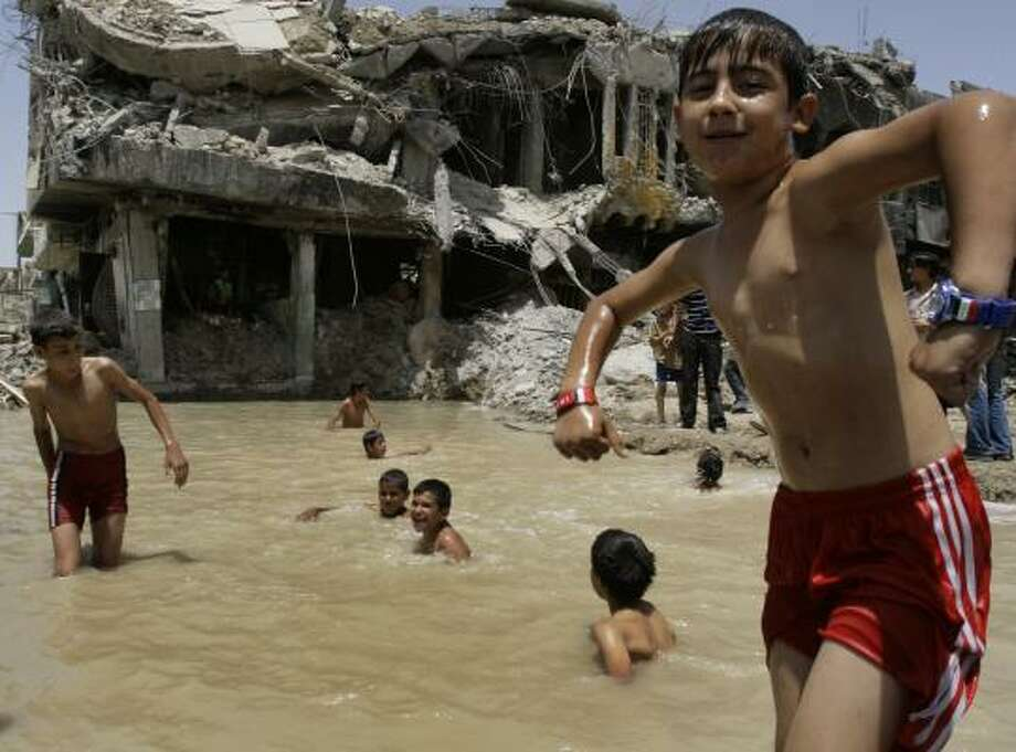 Iraqi boys swim on Tuesday near a house destroyed in the recent fighting in the Shiite enclave of Sadr City in Baghdad. Photo: KARIM KADIM, ASSOCIATED PRESS