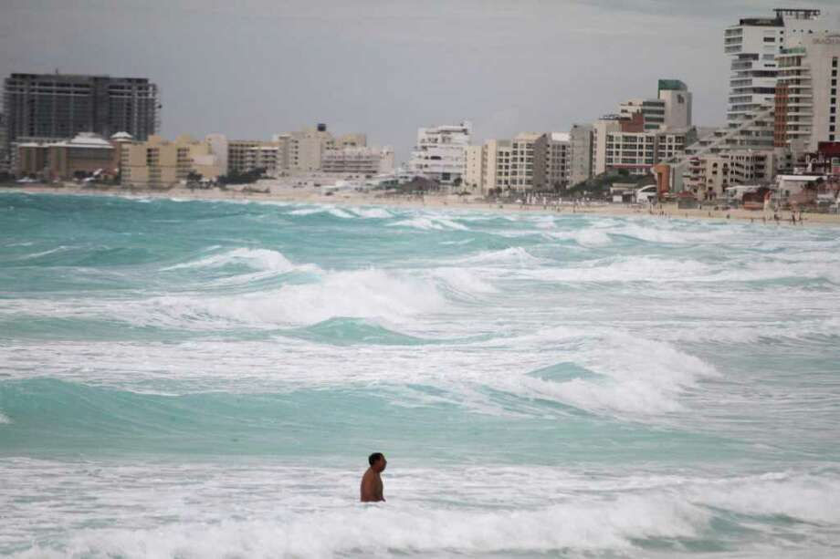 A man swims after the passage of Tropical Storm Don at the Gaviota Azul beach in Cancun, Mexico,Thursday, July 28, 2011. Don is over the central Gulf of Mexico but the system is not expected to become a hurricane as it moves toward southeastern Texas. (AP Photo/Israel Leal) Photo: Israel Leal, Associated Press / AP