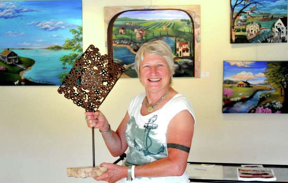 "Arista Baltronis holds ""Inner Glow,""  a sculpture by local artist Bob Hill at the Seti Gallery in Kent, Thursday, July 28, 2011. Photo: Michael Duffy"
