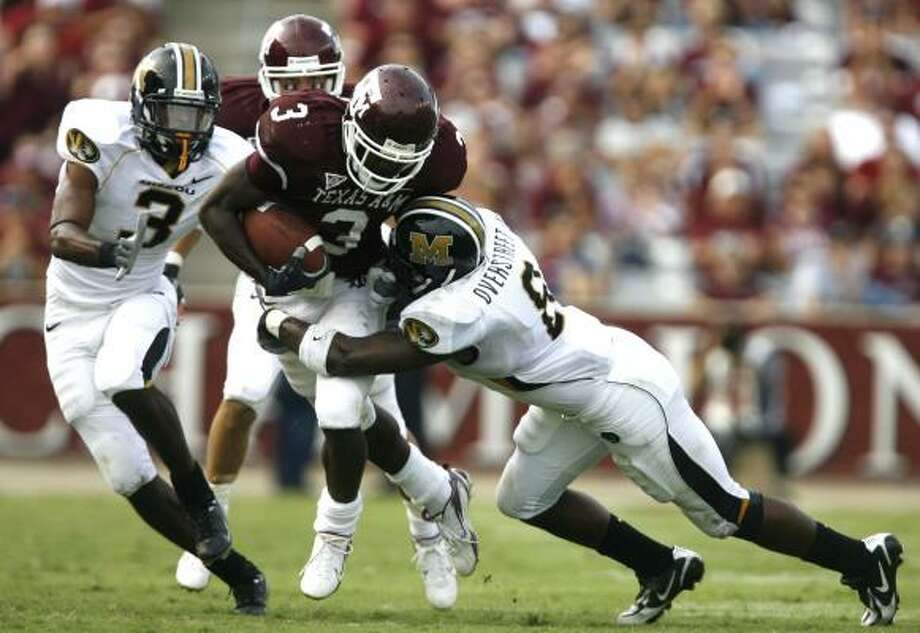 Mike Goodson drags two Missouri defenders with him on a fourth-quarter run. Goodson ran for 65 yards and a touchdown for the Aggies. Photo: Billy Smith II, CHRONICLE
