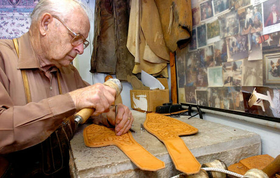 Bob Marrs works on pieces for a saddle in Amarillo. For decades, Marrs has handcrafted saddles for cowhands, world champion steer ropers and celebrities. Photo: MICHAEL LEMMONS, AP