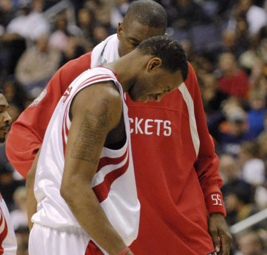 Tracy McGrady is aided by teammate Dikembe Mutombo before leaving the game at Verizon Center. Photo: NICK WASS, AP