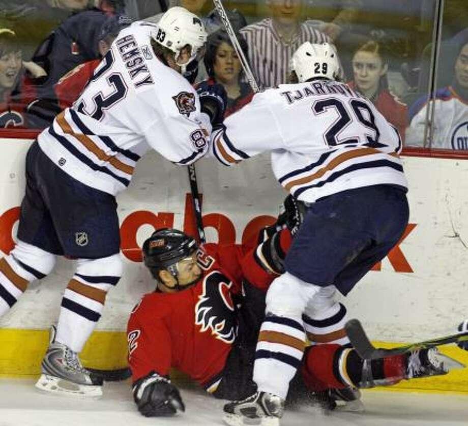 Edmonton's Ales Hemsky, left, and Daniel Tjarnqvist keep Calgary's Jarome Iginla on the ice. Iginla got the upper hand later in Calgary's win. Photo: Jeff McIntosh, AP