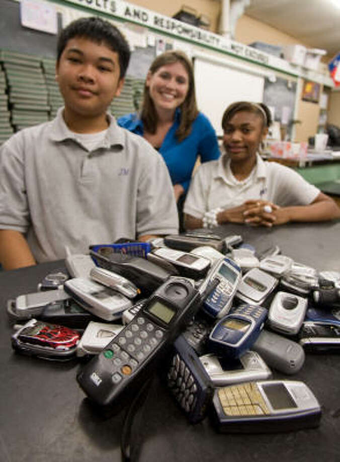 Johnston Middle School pupils, including Paul Guevarra, 14, and Chelsie Stephenson, 14, along with teacher Amber Pinchback, have collected dozens of recyclable cell phones for donation to the Cell Phones for Soldiers program. Photo: R. Clayton McKee, For The Chronicle