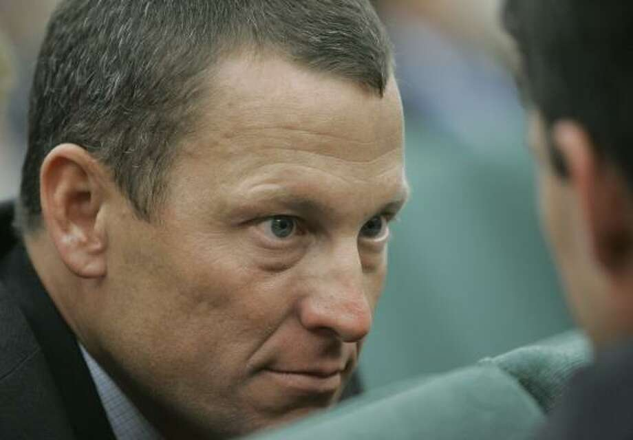 Lance Armstrong listens to a lawmaker while waiting to testify during a meeting Friday of the Senate Finance Committee in Austin.The seven-time Tour de France winner put his celebrity power to work in a late push to get a $3 billion cancer research referendum before Texas voters. Photo: Harry Cabluck, AP