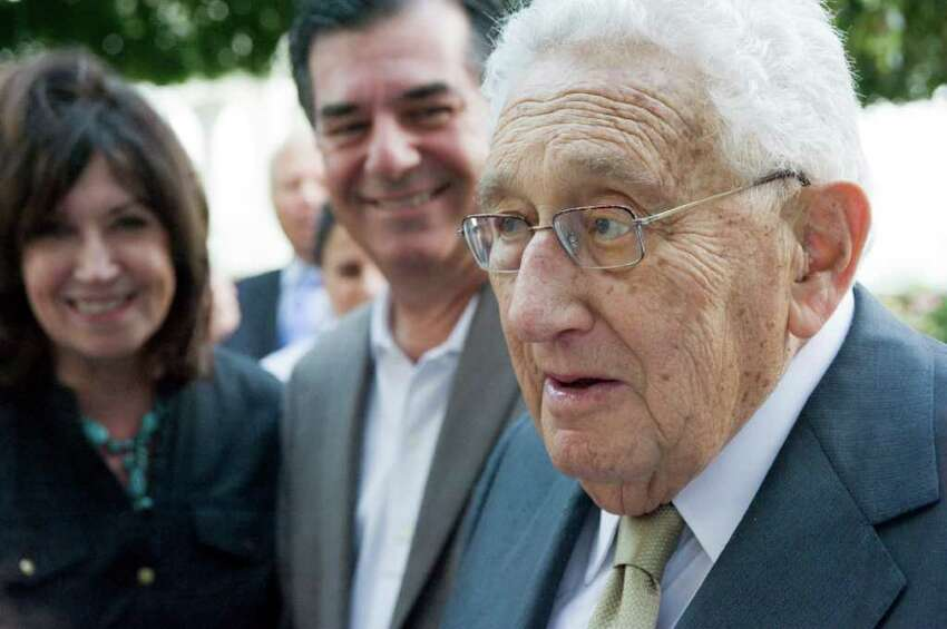 Nobel Prize winner and former Secretary of State Henry Kissinger socializes with Stamford Mayor Michael Pavia and his wife Maureen at Robert Dilenschneider's home in Darien, Conn., July 28, 2011. Kissinger discussed his new book,