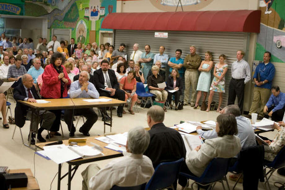 """Karey Bresenhan, standing, a member of the Concerned Citizens' """"Site Selection"""" committee, introduces the committee's presentation at a packed Piney Point City Council """"preagenda"""" meeting at Memorial Elementary School. Photo: R. Clayton McKee, For The Chronicle"""