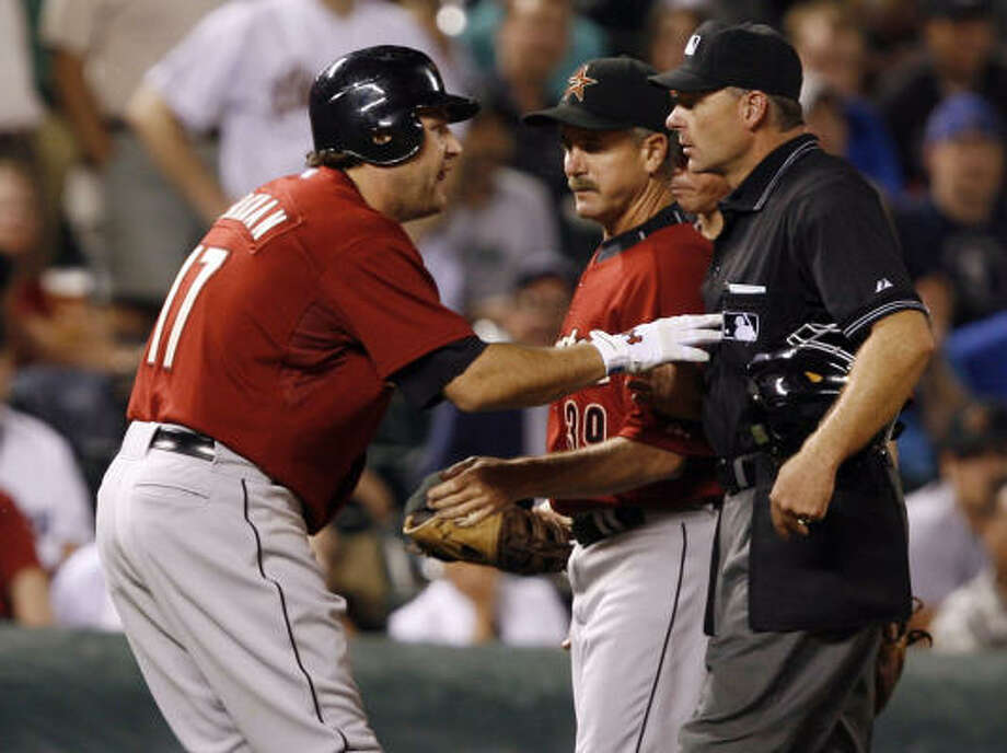 Lance Berkman, left, pleads his case with third base umpire Ed Rapuano, right, after Rapuano called Berkman out on a checked swing to end the eighth inning. Astros coach Doug Mansolino tried to keep Berkman away from the umpire, who ejected the Astros first baseman. Photo: David Zalubowski, AP