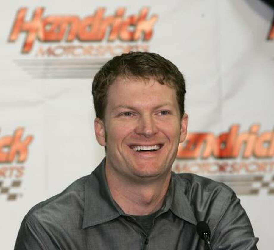 Fans line up at JR Motorsports in Mooresville, N.C., to hear Dale Earnhardt Jr., left, announce that he's joining Jeff Gordon, Jimmie Johnson and Casey Mears at Hendrick Motorsports. Photo: CHUCK BURTON, ASSOCIATED PRESS