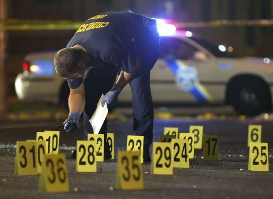 Philadelphia police investigate a double homicide on Sunday. Philadelphia, Baltimore and other East Coast cities are seeing an increase in killings. Photo: JOSEPH KACZMAREK PHOTOS, AP