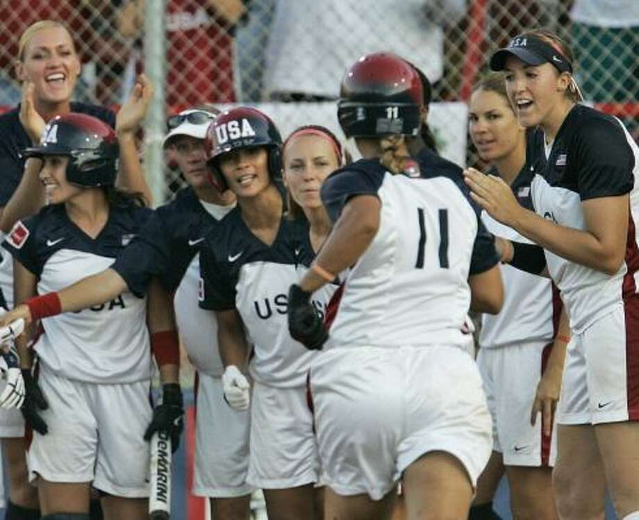 Team USA's Tairia Flowers (11) is greeted at the plate after her two-run homer in the fourth inning against Japan. Photo: ASSOCIATED PRESS