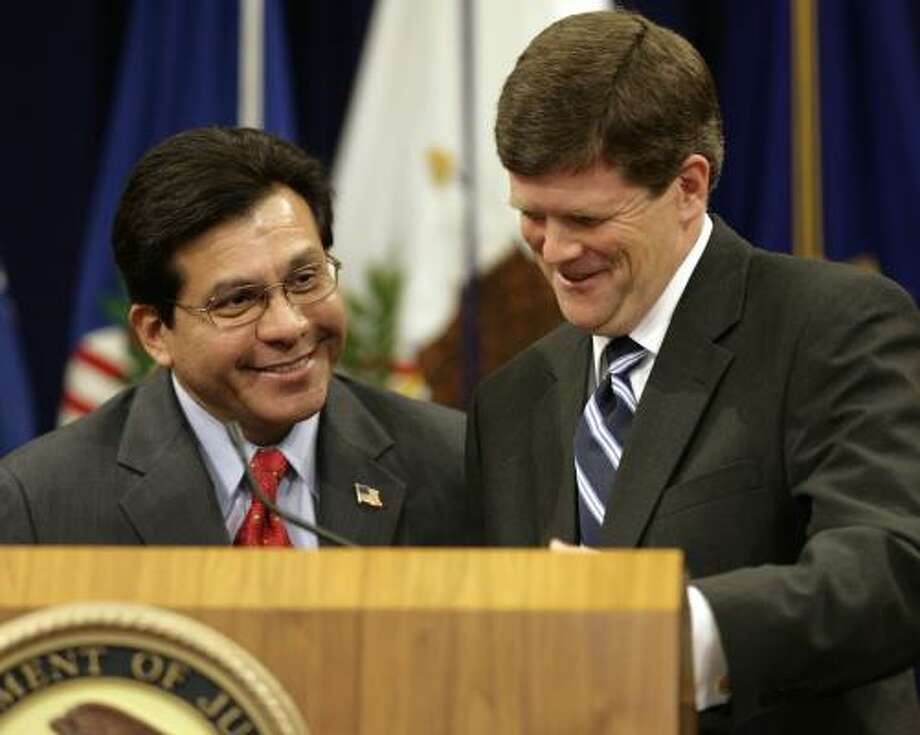 U.S. Attorney General Alberto Gonzales, left, and Deputy Attorney General Paul McNulty mark the fifth anniversary of the corporate fraud task force Tuesday in Washington. McNulty criticized legislation in the House that would bar the government from demanding that companies under investigation disclose confidential talks with legal counsel. Photo: YURI GRIPAS, AFP/GETTY IMAGES