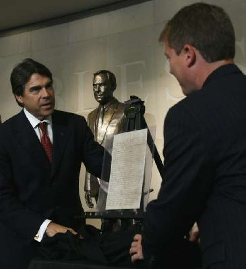 Texas Gov. Rick Perry, left, and Ray Simpson, right, remove the covering at a recent ceremony where a letter purportedly written by Davy Crockett to his children was accepted by the State of Texas for purchase, pending authentication. Some people believe Crockett may not have written it. The state plans to seek forensic experts' help. Photo: Harry Cabluck, AP File