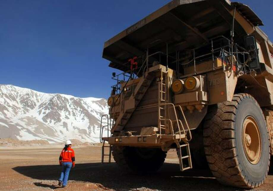 Patricia Guajardo is dwarfed by a truck at Barrick Gold's Veladero mine in Argentina. Driving trucks is an opportunity for many women in the region to overcome inequality. Photo: DIEGO LEVY PHOTOS, BLOOMBERG NEWS