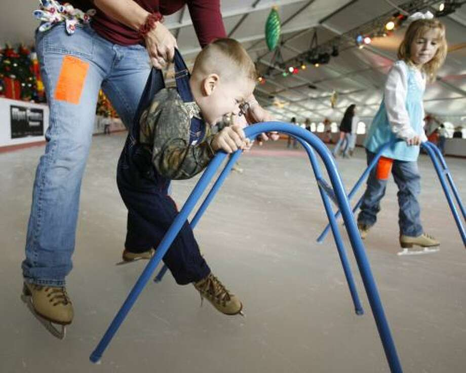 Kandis Dennis, of Montgomery, gives her son, Rett, 3, a lift by his overalls Sunday as her daughter, Allison, 6, uses a walker to steady herself while looping The Ice Rink at The Woodlands Town Center. Photo: MELISSA PHILLIP, CHRONICLE