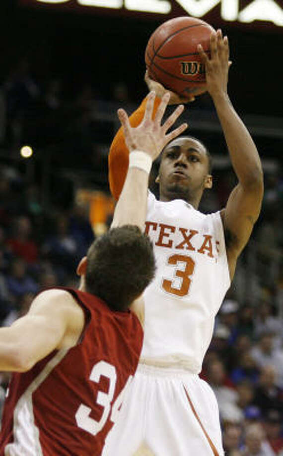 Texas guard A.J. Abrams takes aim over Oklahoma guard Cade Davis for one of his seven 3-pointers against the Sooners. Abrams was the game's leading scorer with 24 points as Texas won 77-49 to advance to the Big 12 conference final. Photo: Ed Zurga, AP