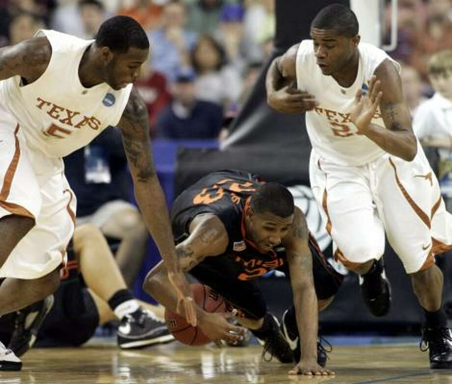 Texas guards Damion James, left, and Justin Mason, right, go for a loose ball against Miami guard James Dews. Photo: Sue Ogrocki, AP