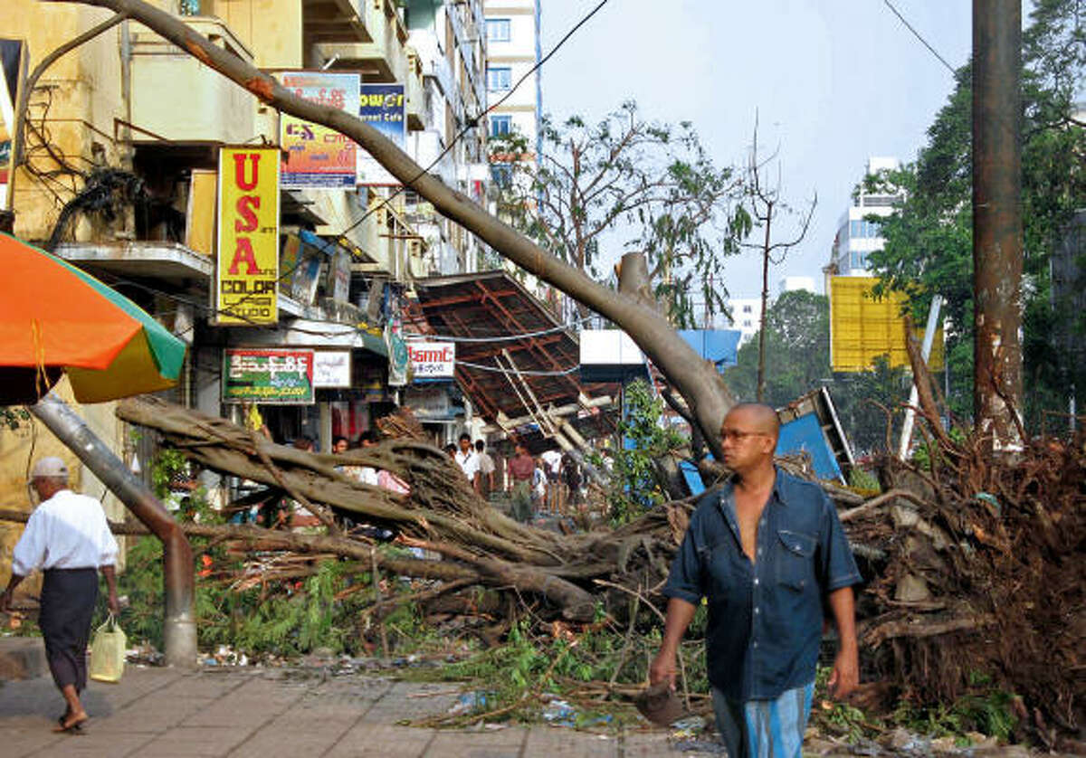 People of Yangon were busy today clearing roads blocked by fallen trees and queuing to collect water from neighbours with private wells, as supplies were cut by the storm.
