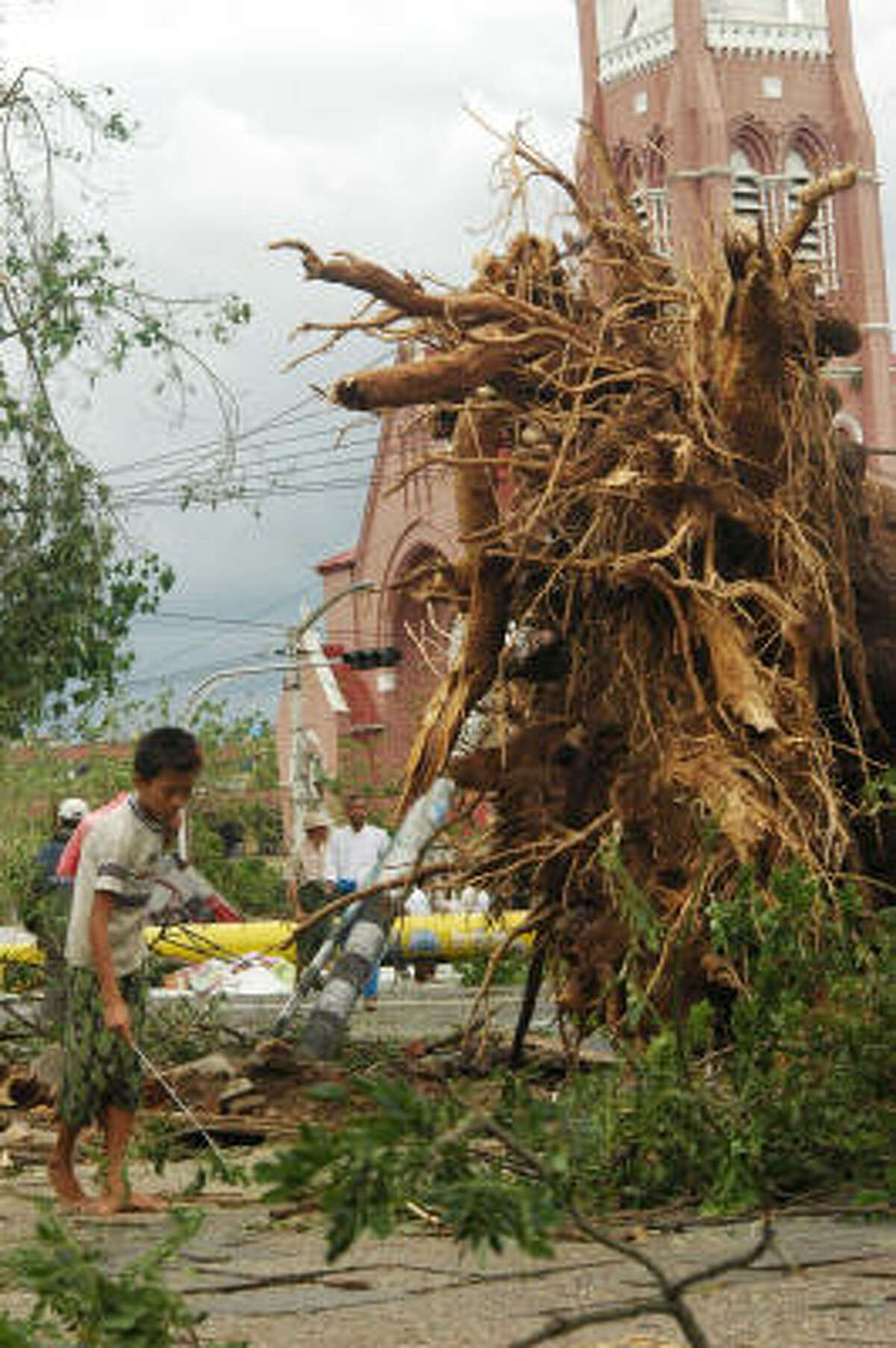 A resident walks near a tree uprooted during cyclone Nargis in Yangon on Sunday. Myanmar residents awoke to devastation after tropical cyclone Nargis tore through swathes of the country, battering buildings, sinking boats and killing at least 350 people, officials said.