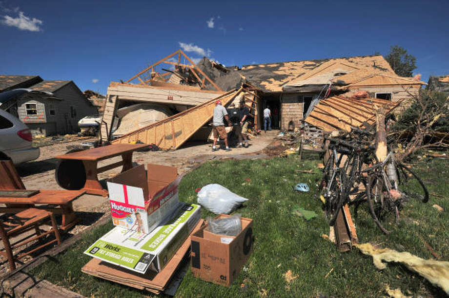 Residents remove personal items and valuables from their tornado-damaged homes in Windsor, Colo., on Saturday. Photo: Bill Ross, Associated Press