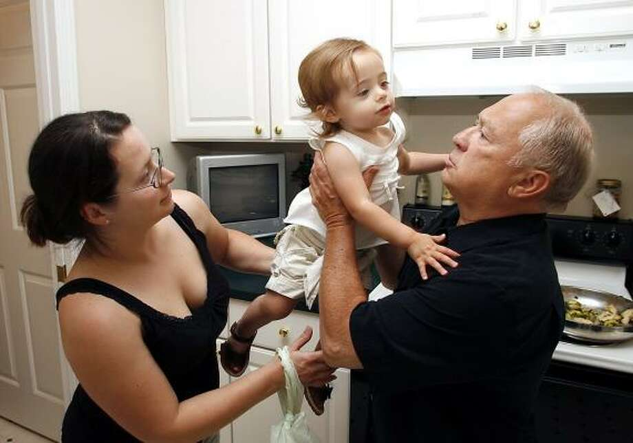 Roger Ghinelli, right, visits with his granddaughter Ava and daughter Denise Mansfield. He can't relocate to a new job until he sells his Sterling Heights, Mich., condominium. Photo: GARY MALERBA, FOR THE CHRONICLE